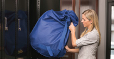 woman putting drycleaning into locker